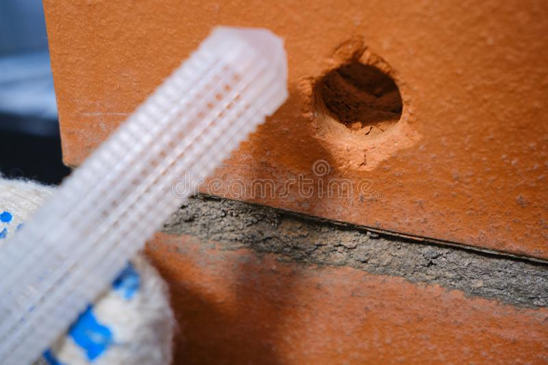 Red hollow brick. Brickwork. Installation of a chemical anchor using a special tool - resin, sleeve and metal angle. Technological. Stage of installation of stock image