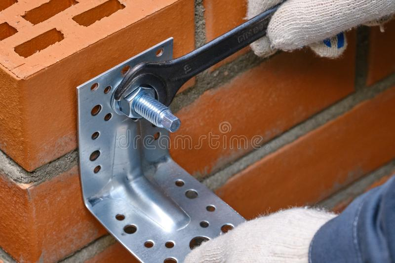 Red hollow brick. Brickwork. Installation of a chemical anchor using a special tool - resin, sleeve and metal angle. Technological. Stage of installation of royalty free stock image