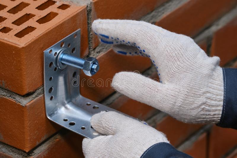 Red hollow brick. Brickwork. Installation of a chemical anchor using a special tool - resin, sleeve and metal angle. Technological. Stage of installation of stock images