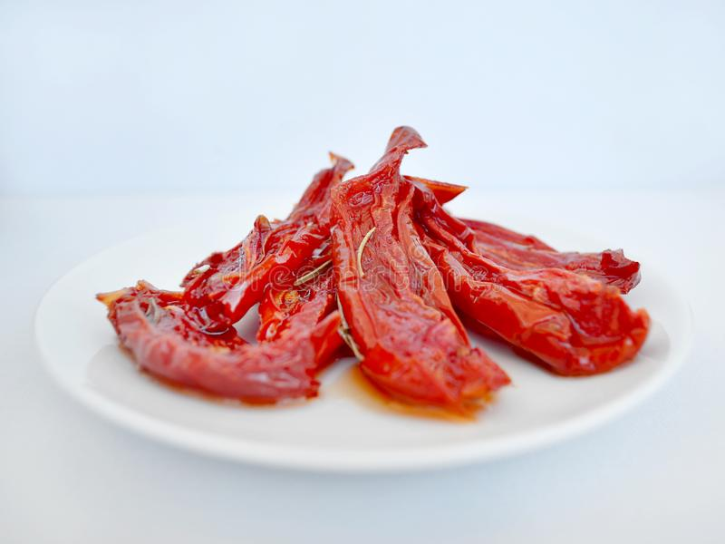 Red homemade oven dried tomatoes with rosemary on a white saucer against a light background, close-up royalty free stock images