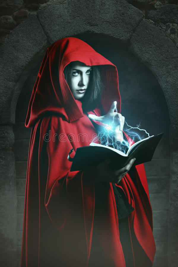 Red hooded woman casting powerful magic. Red hooded woman using powerful magic . Fantasy studio shot royalty free stock images