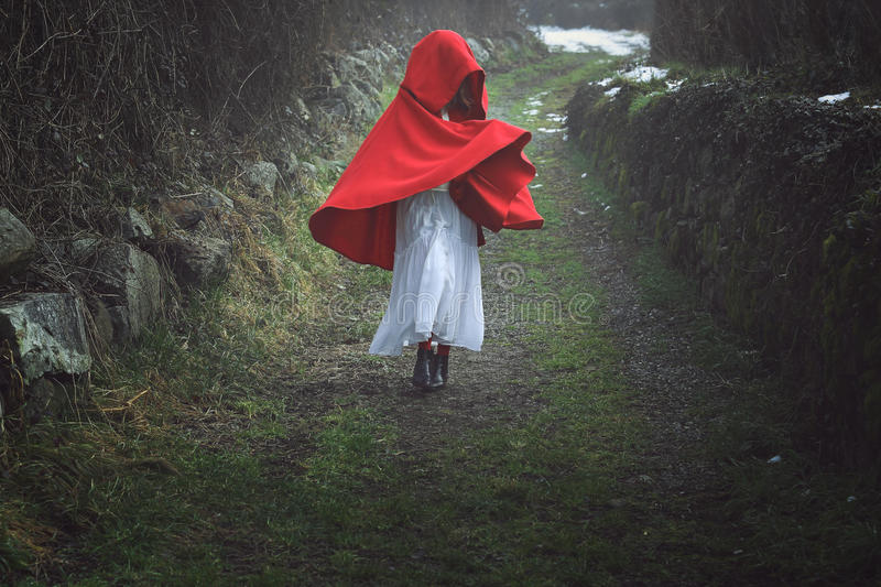 Red hooded woman on a dark country road. Surreal portrait of a red hooded woman on a dark country trail stock images