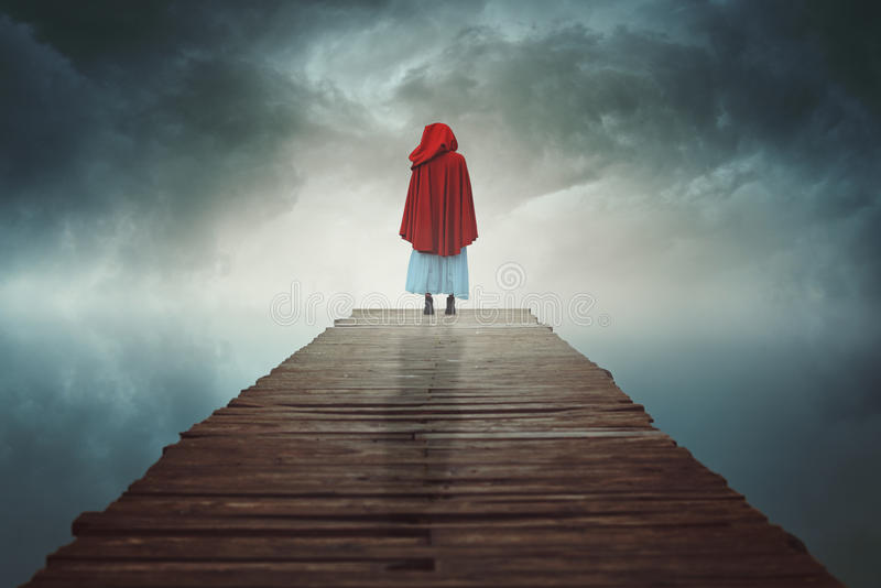 Red hooded woman lost in a surreal land. Red hooded figure lost in a surreal land . Ethereal and fantasy stock photos
