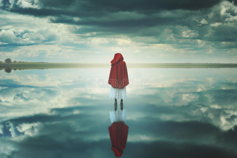 Red hooded woman in a strange landscape with clouds. Fantasy and surreal stock images