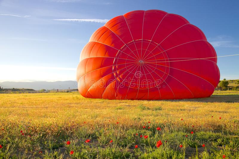 Red Hot Air Balloon Being Inflated. The top of a red envelope from a hot air balloon being inflated on the ground. The envelope sits on a wheat field and there royalty free stock photo