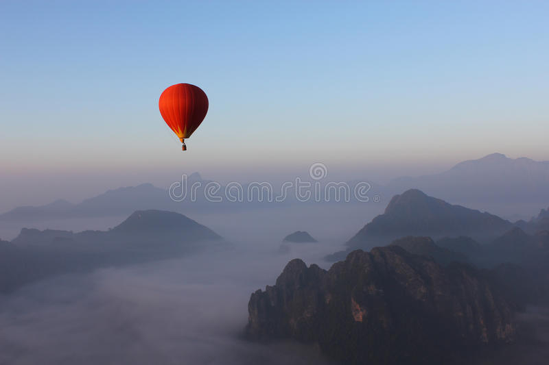 Red Hot-air Balloon float over Misty Mountain in Vang Vieng, Lao stock image