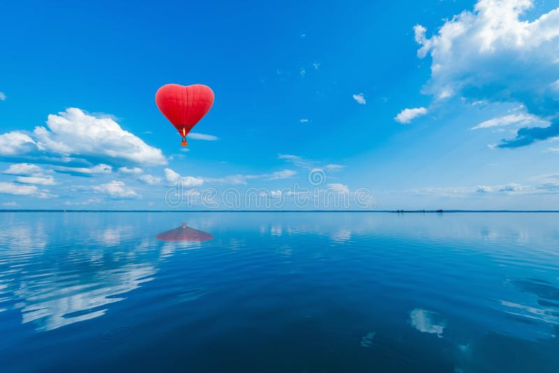 Red hot air balloon in the shape of a heart. Red hot air balloon in the shape of a heart above the lake surface at windless weather time. Present trip on royalty free stock photos