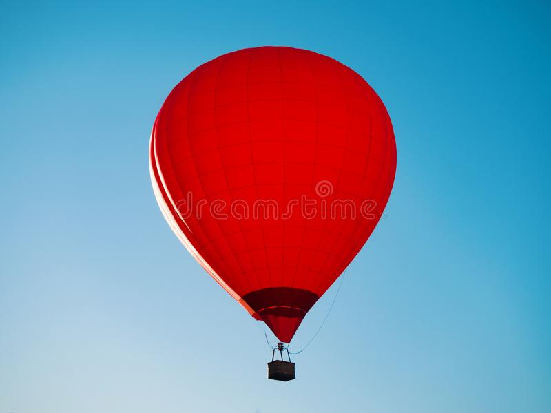 Red hot air balloon with wicker basket. Flying at blue sky background at sunny day royalty free stock photo