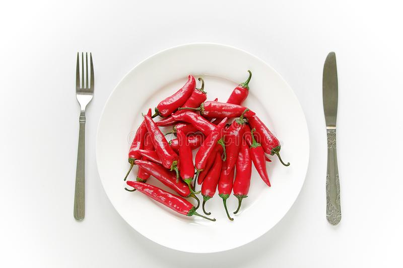 Red hot Cayenne pepper on a white plate, next to a fork and knife. Proper nutrition, vegetarian food, healthy lifestyle concept.  royalty free stock photo