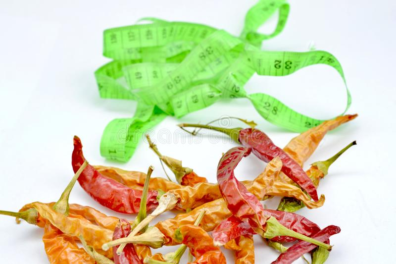 red hot chili pepper in front of tape measure stock images