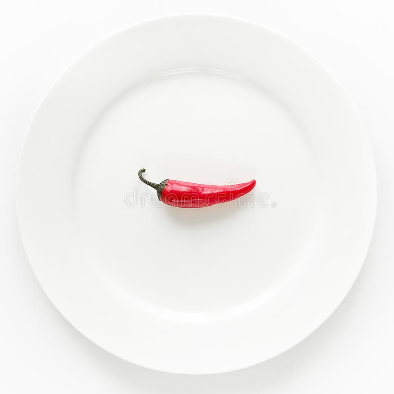 Red hot chili pepper on white plate on white background stock photos
