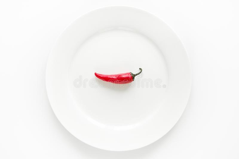 Red hot chili pepper on white plate on white background stock image