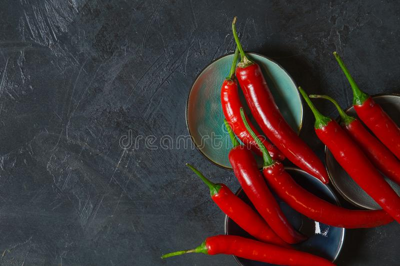 Red Hot Chili Peppers in bowls on old background stock photos