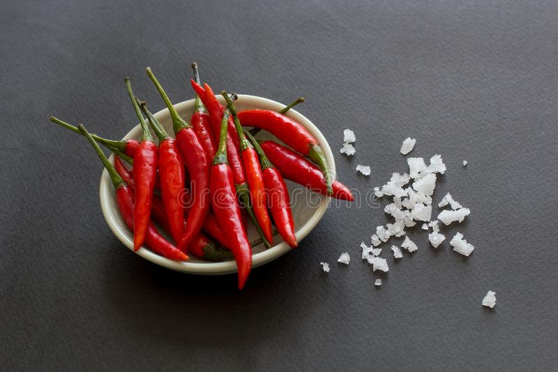 Red hot chili peppers on a green plate with salt crystals nearby on a black background. Asian species stock photo