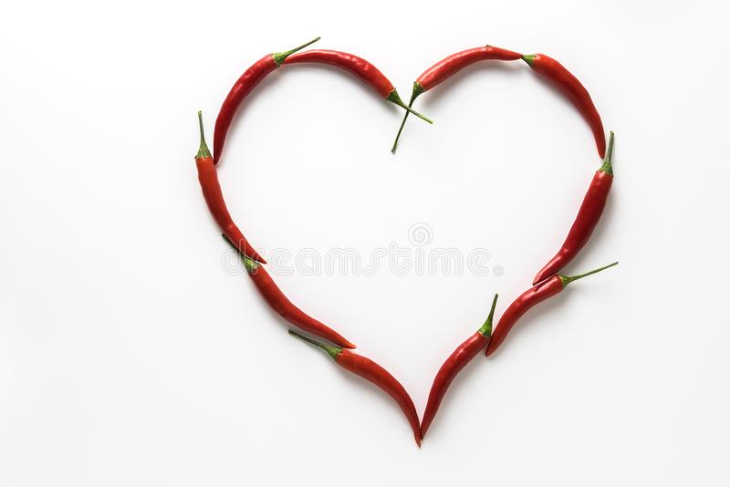 Red hot chili peppers in the shape of a heart symbolizing love isolated on white background. Red hot chili peppers in the shape of a heart symbolizing love stock photos
