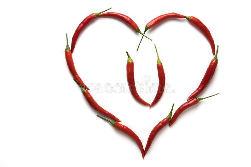 Red hot chili peppers in the shape of a heart symbolizing love isolated on white background. Red hot chili peppers in the shape of a heart symbolizing love royalty free stock image
