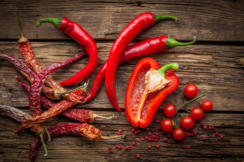 Red hot chili peppers, sweet pepperon wooden table royalty free stock photography