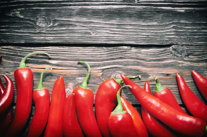 Red hot chili peppers on wood background. Chili pepper on wood background spice food spicy table red ingredient peppers crop cutting board hot paprika culture stock photography