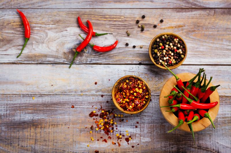 Red hot chilli pepper pods in a wooden mortar, pepper flakes and peppercorns in wooden bowls royalty free stock images