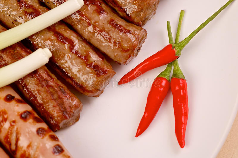 Red hot chilli peppers with grilled sausages and royalty free stock photography