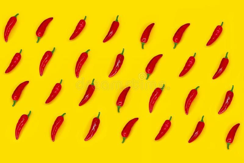 Red hot chilli peppers pattern on yellow background. Flat lay. Top view stock photography