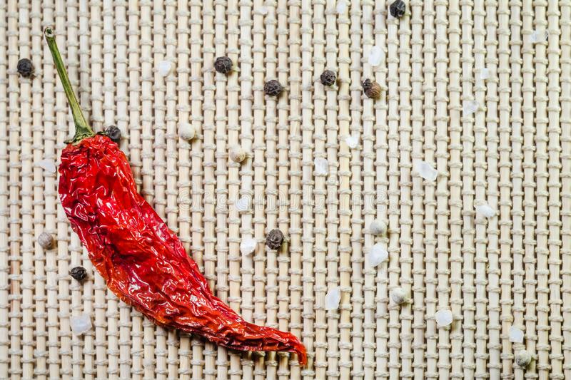 Red hot dried pepper, sea salt, white and black peppercorns on a bamboo serviette. With copy space stock images