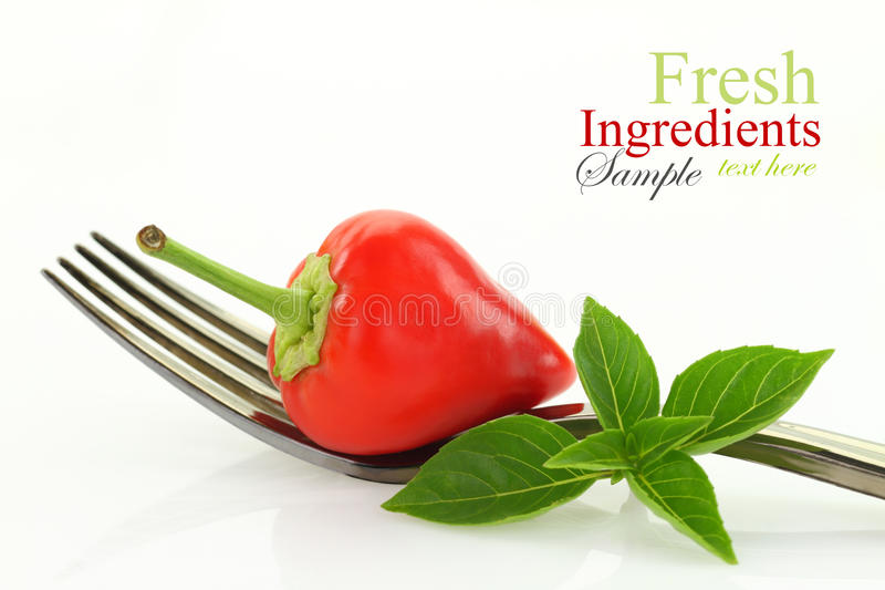 Red hot mini chili pepper and basil on fork royalty free stock images