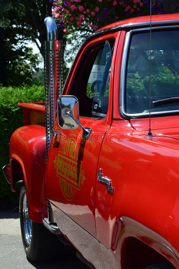 Red Hot rod pickup truck. Red Hot rod pick up truck with chrome tailpipe pointing up, flower background royalty free stock photos
