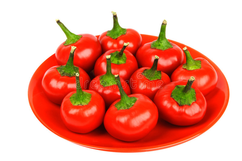 Red hot spicy peppers. On the red plate royalty free stock images