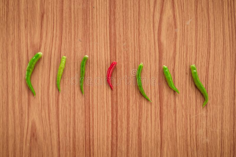 A Red hot spicy thai chili peppers or Mirchi among green chilli arranged in a horizontal row on wooden background, flat lay. Top stock photo