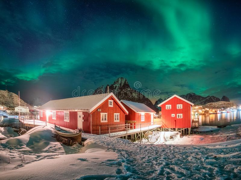 Red house in fishing village with aurora borealis over arctic ocean in winter at night royalty free stock photos