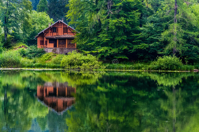 Red house on the lake royalty free stock photo