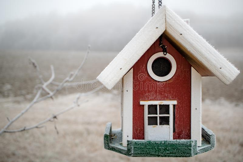 Red house-like bird feeder with frost stock photo
