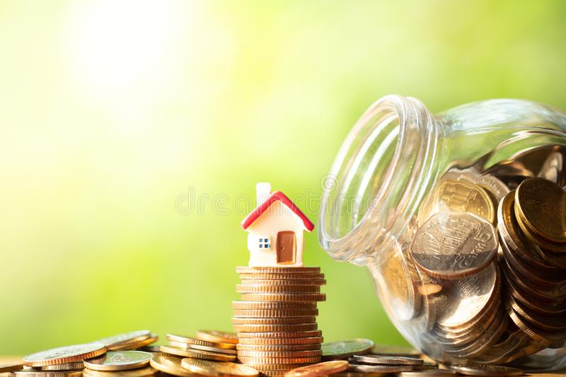 Red house shape figure on stack and pile of coins. Beside glass jar or piggy bank on wooden table on greenery blurred background with copy space. Business royalty free stock images