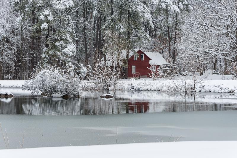 Red house in snow behind a frozen pond stock photo