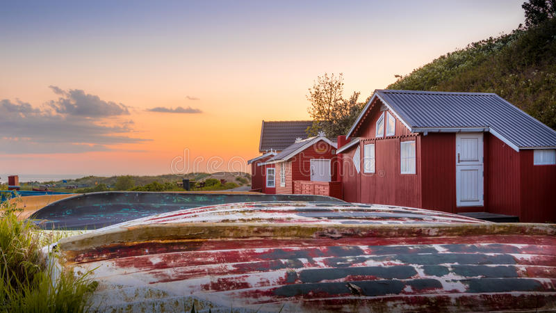 Red houses in field at sunset stock photo