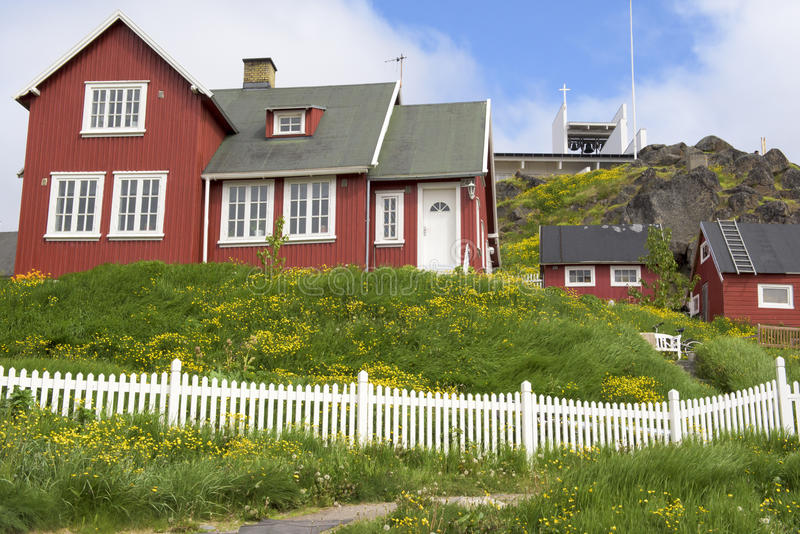 Red houses, Greenland. Red houses, green meadows, yellow dandelion blue sky in Qaqortoq, Greenland royalty free stock photography