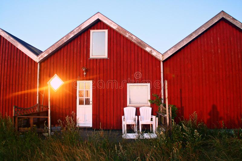 Red houses in the sunset. Red wooden houses in the sunset. Two chairs in front and the sunlight reflected in the window stock photo