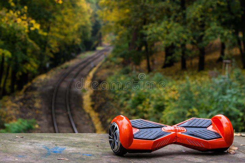 Red hoverboard against the background of railroad rails. The red hoverboard against the background of railroad rails royalty free stock photos