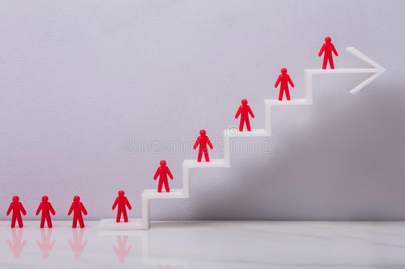 Red Human Figures On Increasing Graph. Red Human Figures Standing On Increasing White Arrow Graph In Front Grey Background royalty free stock photos