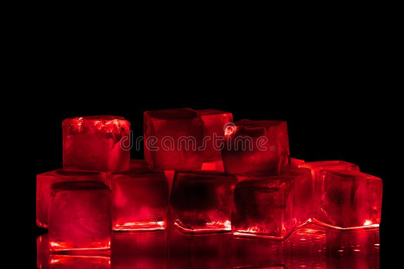 Red ice cubes on black background  closeup, transparent frozen burgundy wine color water with red backlight and reflection. Abstract cold alcohol drinks royalty free stock photos