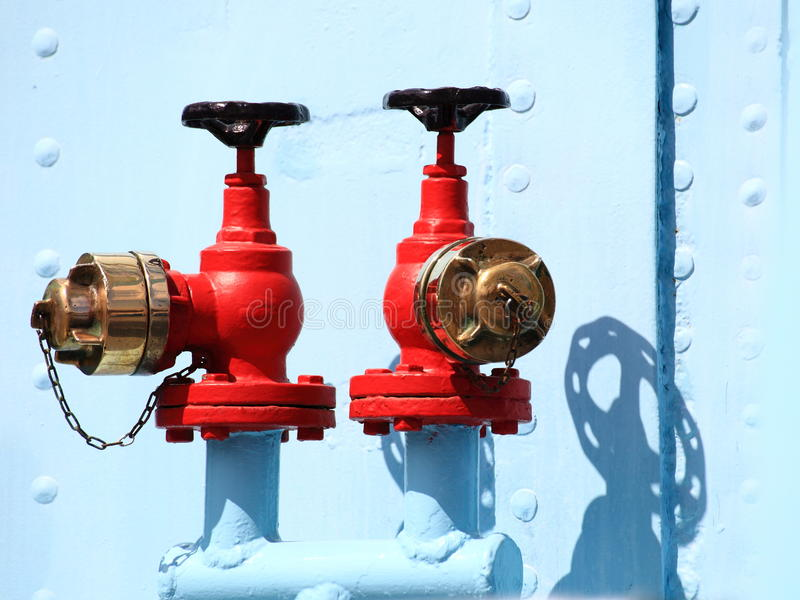 Red industrial faucet wheel. On blue background, nobody stock images