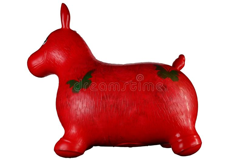 Red inflatable horse for jumping in the game room of the kindergarten isolated on black background royalty free stock images