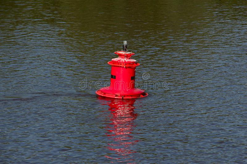 Red buoy in the water. Red iron buoy with a signal lamp swinging on the waves stock images