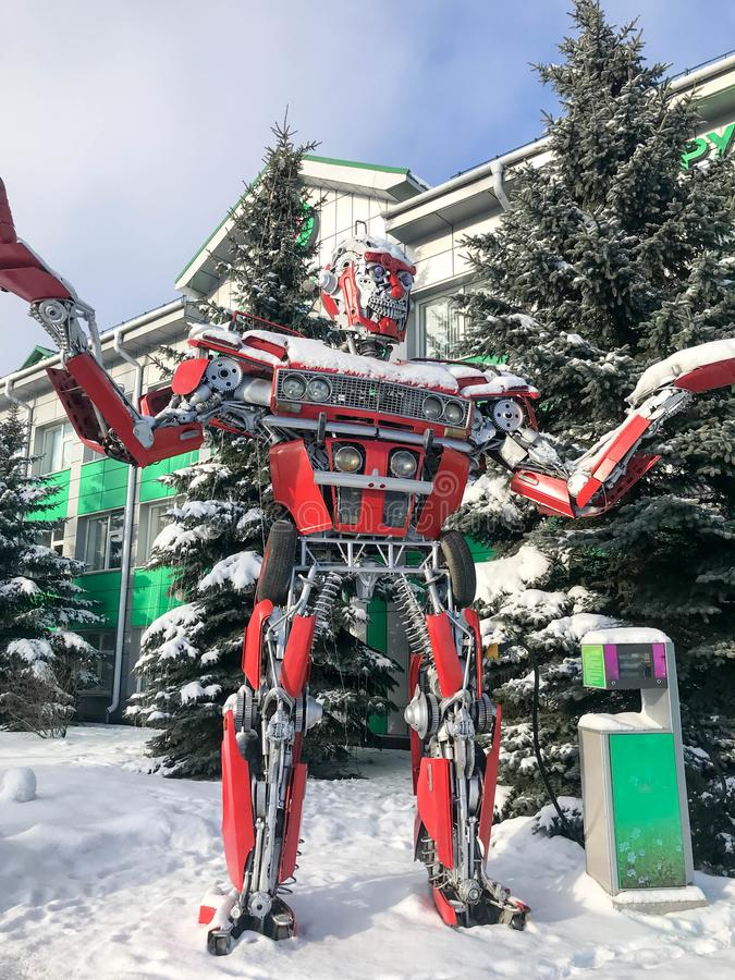 Red iron metal big strong dangerous fantastic, futuristic humanoid robot from a car with hands and head in winter.  royalty free stock photo