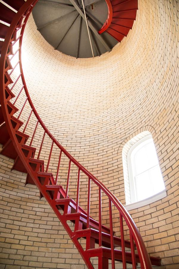 Red iron spiral staircase inside a lighthouse royalty free stock image