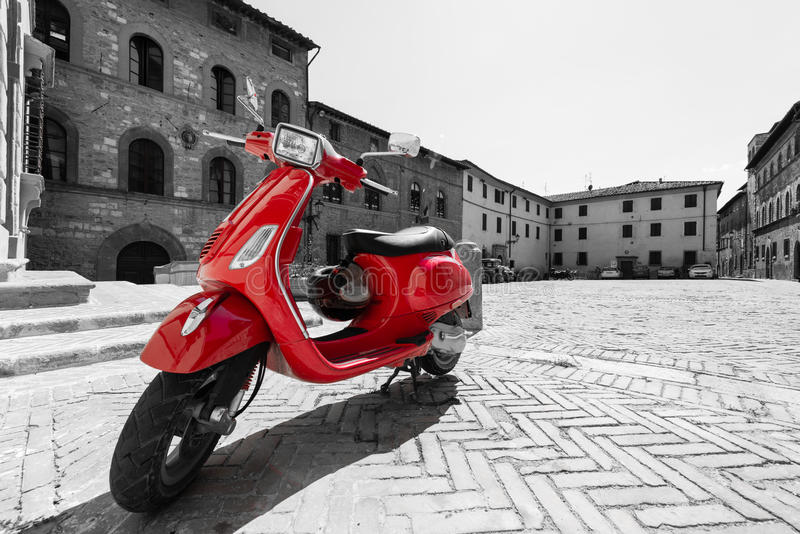 Red Italian scooter. In the historical centre of the Tuscan town of Colle di Val d'Elsa - red scooter with black and white surrounding royalty free stock images