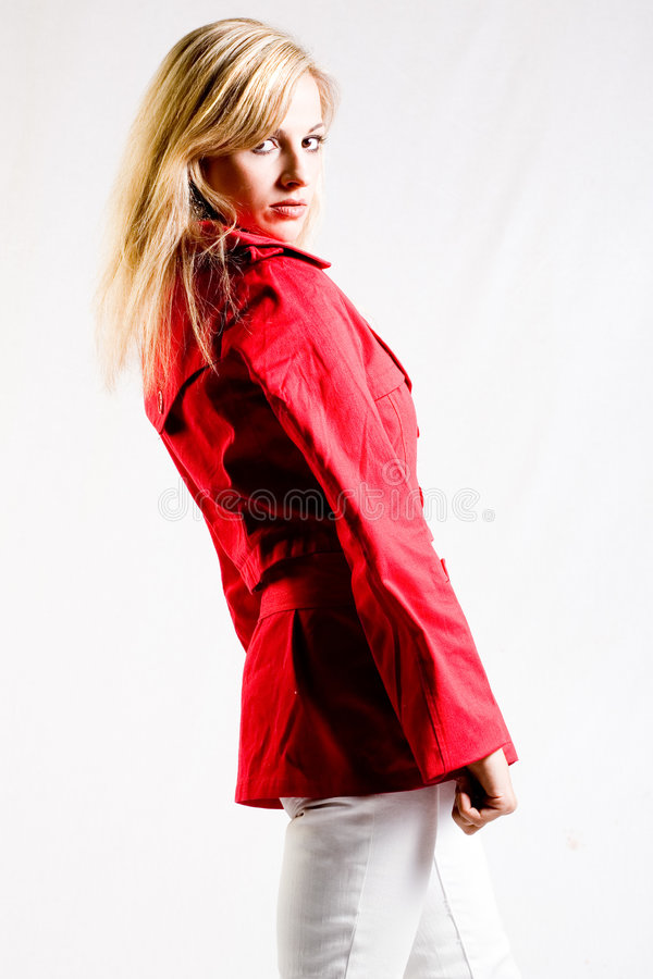 Red jacket. Blond woman in bright red jacket in studio stock image