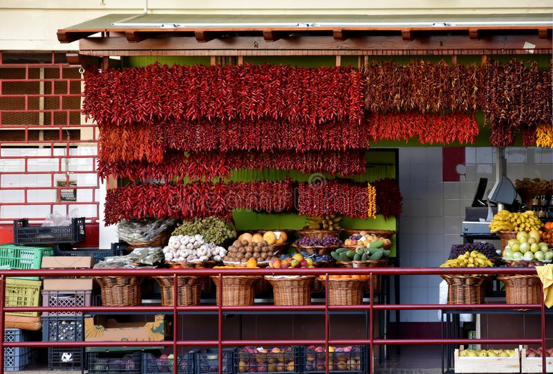 Red chili for sale. Red jalapeno peppers hanging for sale in the market hall in Funchal, Madeira royalty free stock image