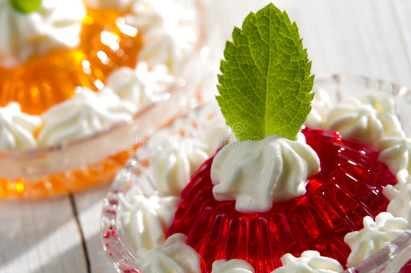 Red jelly with cream and mint leaf royalty free stock photo